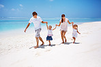 Young family running on the beach