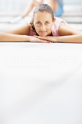 Smiling woman lying on the floor at the gymnasium