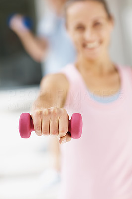 Female with a dumbbell at the gym , focus on the hand