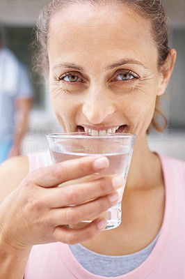 Closeup of a smiling female drinking a glass of water