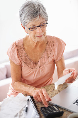 Busy old woman using calculator to pay monthly bills