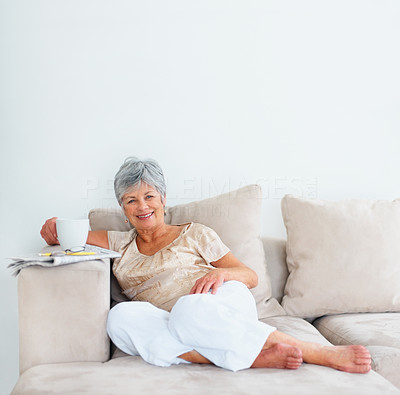 Happy old woman drinking coffee while relaxed on the couch
