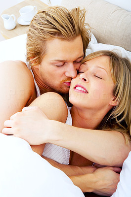 Buy stock photo Young couple embracing in bed. A sensual and cute couple.
