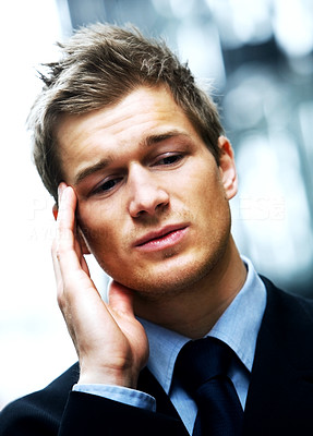 Buy stock photo Worried Businessman with headache holding his forehead