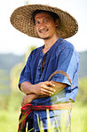Portrait of a rice plantation worker holding a scythe - Thailand