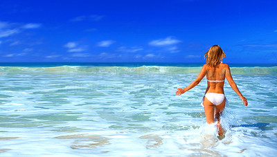 Buy stock photo Picture fo a beautiful beach in the tropics, with a woman walking out into the water.