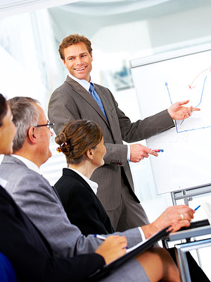 Buy stock photo A mature business man giving a presentation to some colleagues.