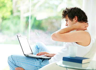 Young man working on laptop in morning at home