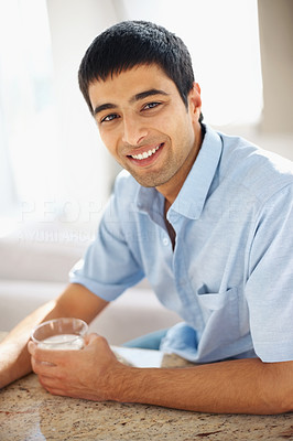 Smiling young guy holding a glass of water looking at you
