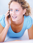 A happy pretty young girl smiling and talking on mobile phone