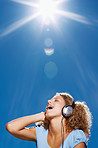 Closeup of  happy young lady listening to music outdoors