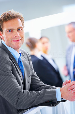 Buy stock photo Mature businessman smiling with his colleagues in the background
