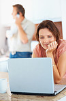Woman using laptop while man on phone in the background