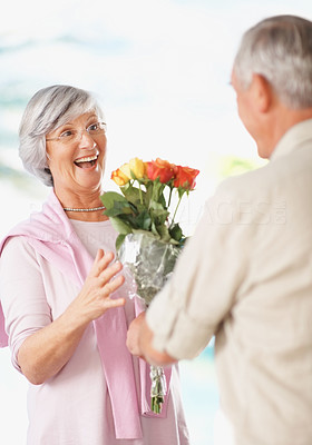 Senior man giving bouquet to his surprised wife
