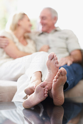 Couple sitting on sofa with feet propped on table, focus on feet