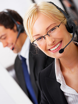 Buy stock photo Portrait of a beautiful business woman with a male colleague in the background.