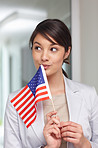 Young patriotic woman with an American flag , lost in thought