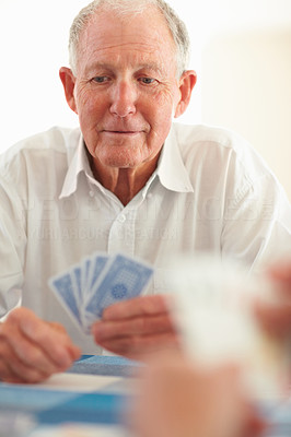 Retired man playing a game of cards