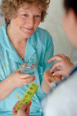 Old woman being given a health pill by a doctor
