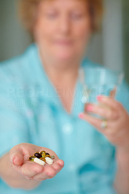 Blur image of a woman offering a handful of health pills