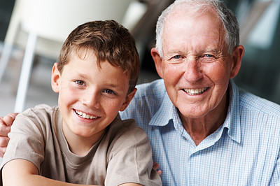 Buy stock photo Portrait of a happy young boy sitting with his grandfather and smiling