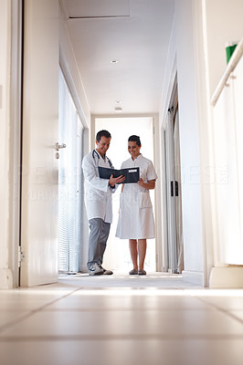 Doctor and nurse going through a report while at a corridor