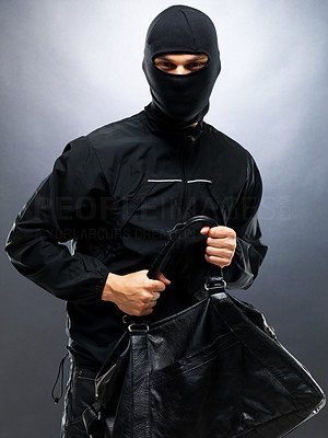 Buy stock photo Portrait of a young male thief stealing a handbag against grey background