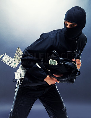 Buy stock photo Portrait of a young male thief stealing money from bank
