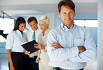 Confident business executive with colleagues working at the back