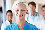 Young lady nurse and her team standing behind