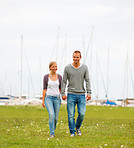 Happy young couple walking on a grass field, harbour view at the back