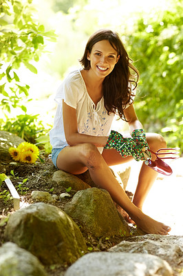 Buy stock photo Portrait of beautiful young female sitting on rocks and holding gardening tools outdoor