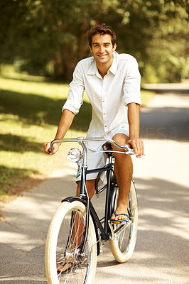 Buy stock photo Full length shot of a young man cycling in the park