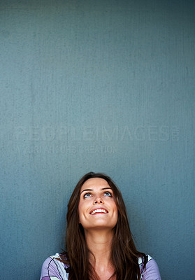 Buy stock photo Young woman looking up at copyspace against grey b