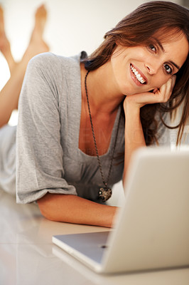 Buy stock photo Relaxed young woman using laptop while lying on fl