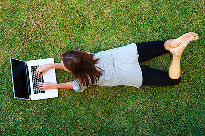 Buy stock photo Young woman lying on grass working on laptop