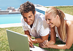 Smiling young couple using laptop outdoors