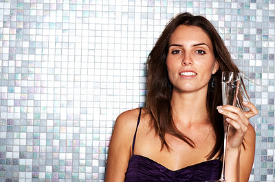 Buy stock photo Portrait of a young woman gazing at the camera while holding up a glass of champagne