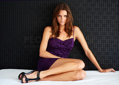 Buy stock photo Portrait of an attractive woman sitting on a bed and looking alluringly at the camera