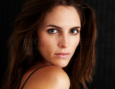 Buy stock photo Closeup portrait of an attractive young woman looking at the camera over her shoulder