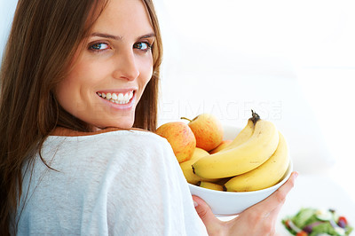 Buy stock photo An attractive young woman holding a fruit bowl