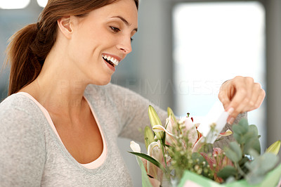 Buy stock photo Pretty happy young lady with a bouquet reading a c