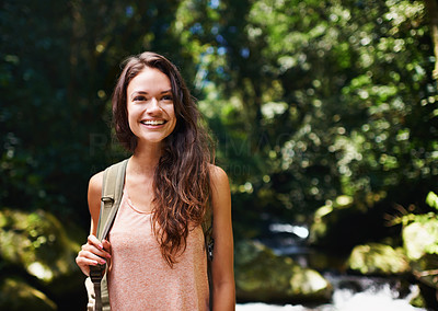 Buy stock photo Shot of a beautiful young woman hiking through the forest