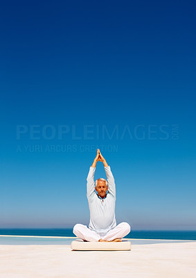 Retired man practicing yoga on the beach with his hands raised
