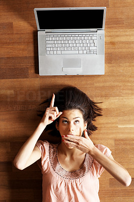 Buy stock photo Surprised young lady pointing at laptop screen above her head while lying on the floor - copyspace