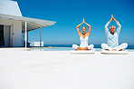 Mature couple practicing yoga by a beach house