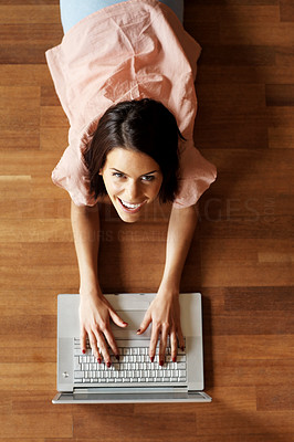 Buy stock photo Smiling young female lying on floor using laptop