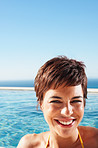 Happy young woman at the swimming pool during her vacation