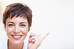 Closeup: Happy business woman pointing at copyspace