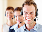 Young call centre guy with colleagues at the back